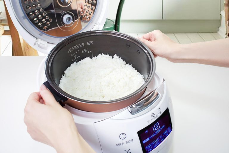 Hanads lifting Ninja ceramic bowl from Sakura white rice cooker